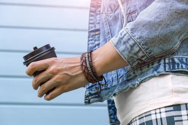 コーヒー、カフェイン中毒、夏のテイクアウト紙コップを保持している手首とジーンズのデニムジャケットに自由奔放に生きるレザーブレスレットを身に着けているヒッピー女性。 Premium写真