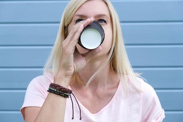 持ち帰り用の紙コップ、フリーピープルライフスタイルコンセプトからホットコーヒーを飲みながら手首に自由奔放に生きる革ブレスレットを身に着けているヒッピー女性。 Premium写真