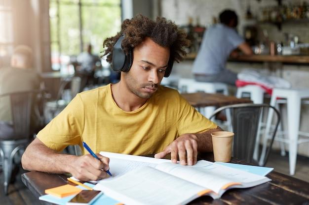Ragazzo afroamericano hipster con libro e quaderno che ascolta la musica in cuffia e beve caffè mentre era seduto in un accogliente ristorante. concetto di educazione Foto Gratuite