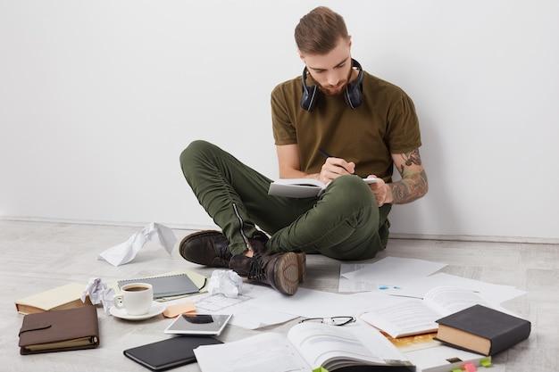 入れ墨をしたヒップスターのひげを生やした男、カジュアルな服を着て、勉強に忙しいブーツ 無料写真