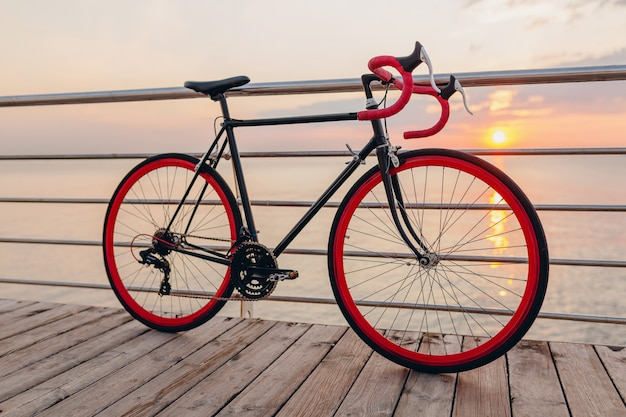 Hipster bicycle in morning sunrise by the sea Free Photo