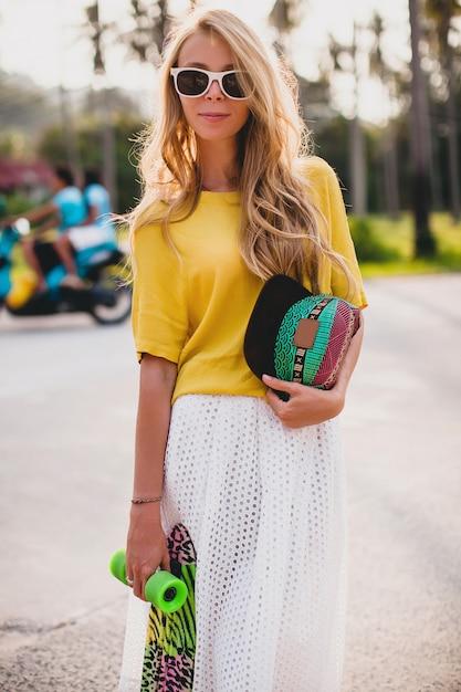 Donna fresca hipster con skateboard e cappuccio in posa sorridente in vacanza Foto Gratuite