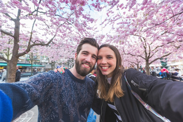 Hipster couple taking a selfie in stockholm with cherry blossoms Premium Photo