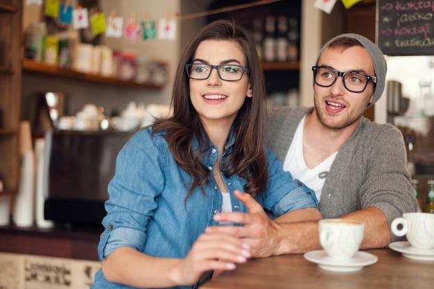 Coppia di hipster parlando con gli amici al caffè Foto Gratuite