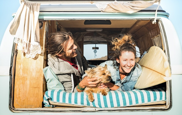 Hipster couple with cute dog traveling together on vintage mini van transport Premium Photo