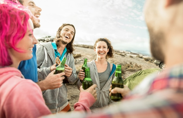 Hipster friends having fun together at beach camping party Premium Photo