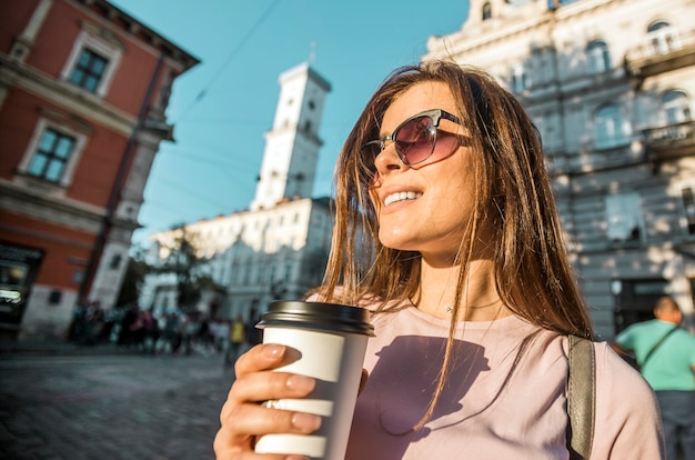 Hipster girl in sunglasses holding coffee cup Premium Photo