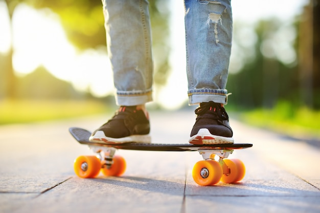 Hipster girl with skateboard outdoors. closeup skateboarding. active sporty woman having fun in park Premium Photo