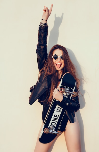 Hipster girl with skateboard Free Photo