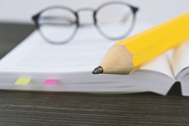 Hipster glasses for reading on an open book with big yellow pencil Premium Photo