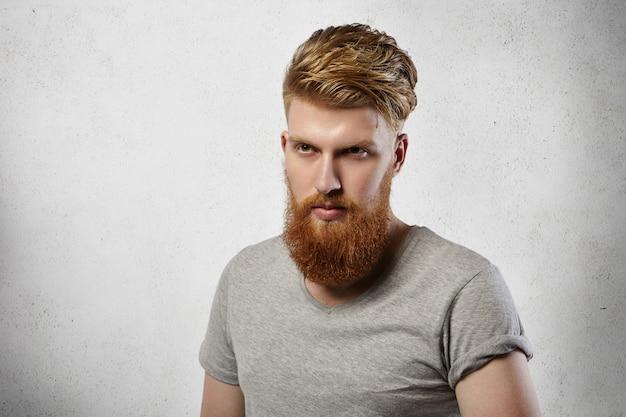 Uomo hipster in maglietta grigia che guarda avanti a lui con espressione determinata, pensando ai suoi piani e obiettivi futuri. Foto Gratuite