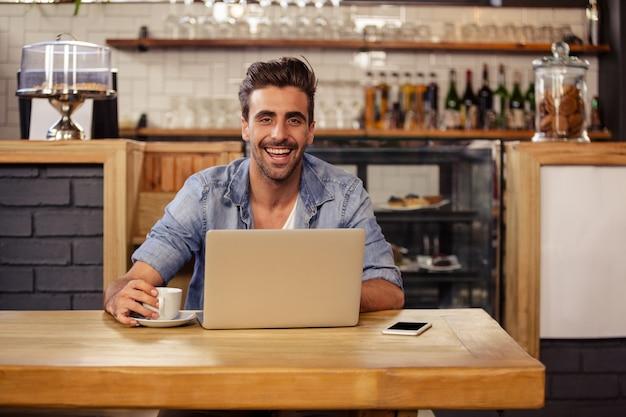 Hipster man smiling while using laptop Premium Photo