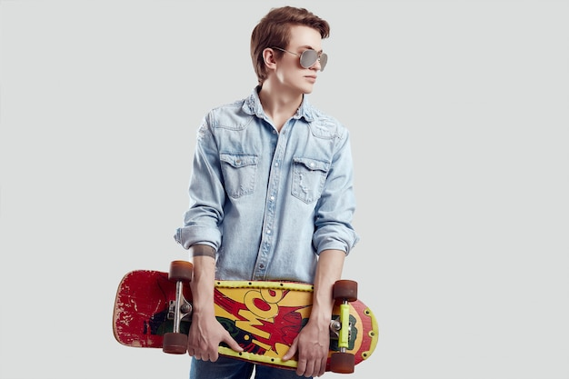 Hipster man in sunglasses and jeans jacket posing with skateboard Premium Photo