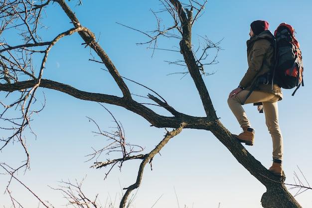 流行に敏感な男のバックパックで旅行、空を背景に木の上に立って、暖かいジャケット、アクティブな観光客を着て、寒い季節に自然を探索 無料写真