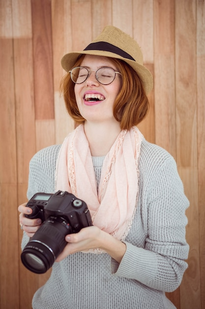 Hipster smiling and holding camera Premium Photo