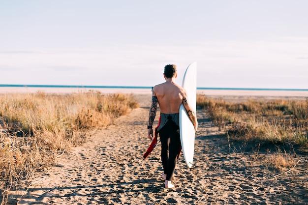 サーフボードとビーチで流行に敏感なトレンディなサーファー 無料写真