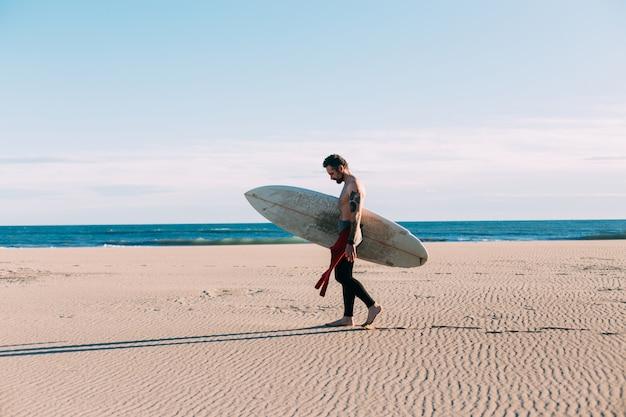Хипстерский модный серфер на пляже с доской для серфинга Бесплатные Фотографии