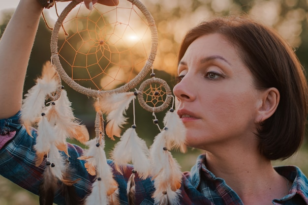 Hipster woman in the form of a shaman is looking for inspiration from mother earth in a wigwam in nature. Premium Photo