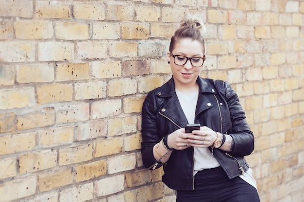 Hipster woman typing on smart phone in london. Premium Photo