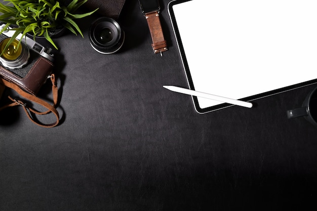 Hipster workspace with vintage camera, films, and blank screen tablet on desk Premium Photo