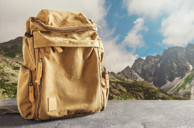 Hipster yellow backpack on the table against the mountains. hiking in the mountains concept Premium Photo