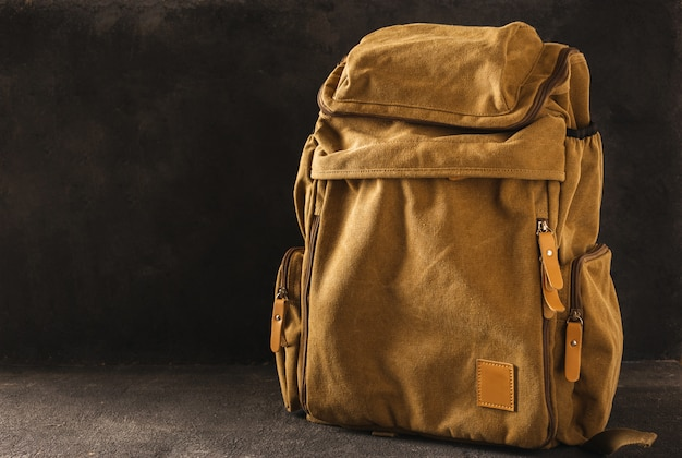 Hipster yellow backpack on table copy space Premium Photo