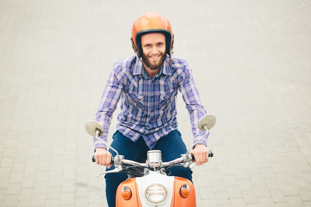 Hipster young  man in helmet is riding on yellow retro scooter in town Premium Photo
