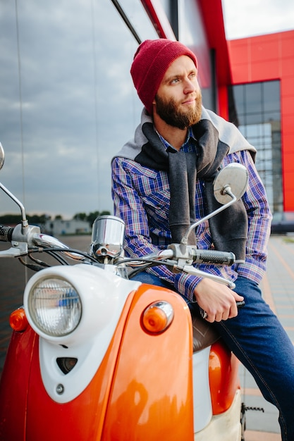 Hipster young  man in helmet is riding on yellow scooter in town. Premium Photo