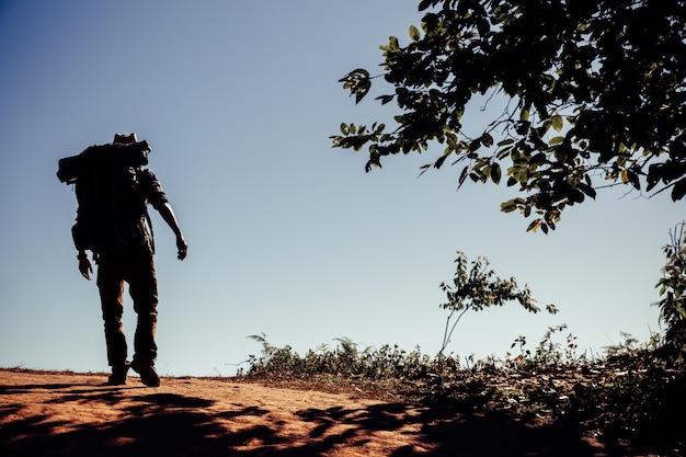ピーク山の夕日を楽しんでいるバックパックと流行に敏感な若い男。 無料写真