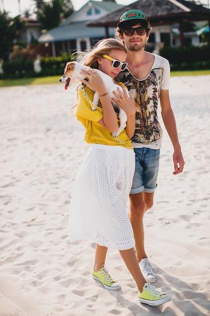 Хипстерская молодая стильная хипстерская пара в любви гуляет и играет с собакой на тропическом пляже Бесплатные Фотографии