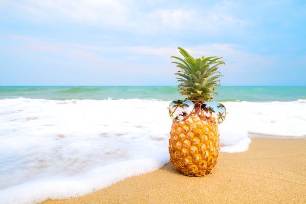 Hipster ананас с очками на песчаном пляже Premium Фотографии