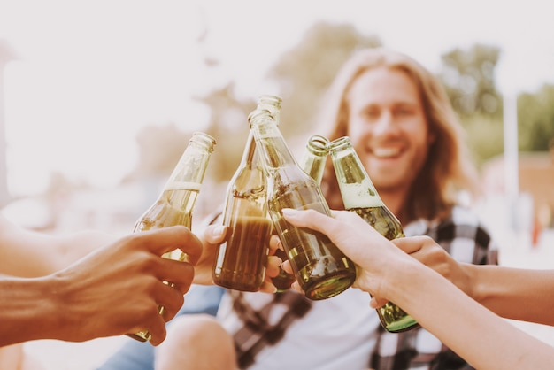 Hipsters drink beer on beach in sunlight. Premium Photo