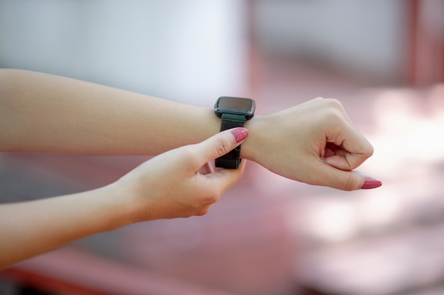 His hands and black wristwatch knowing the time, concept, time Premium Photo
