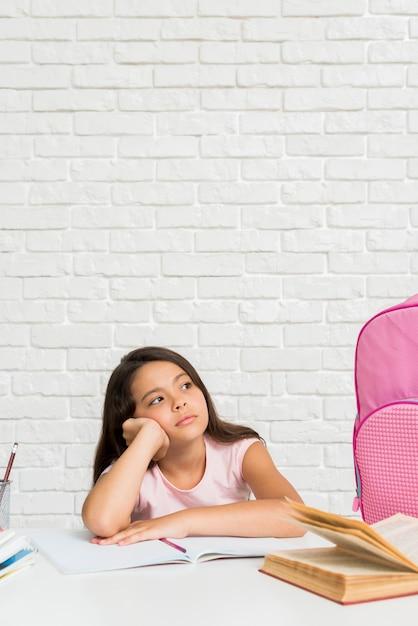 Hispanic bored schoolgirl sitting at desk Free Photo