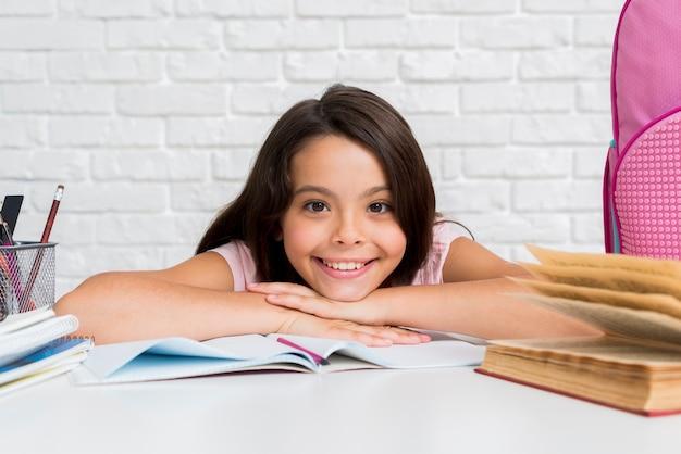 机に座っているヒスパニックの陽気な女の子 無料写真