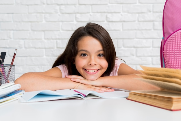 Hispanic cheerful girl sitting at desk Free Photo