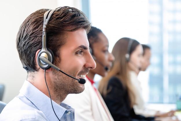 Hispanic man in call center office with team Premium Photo
