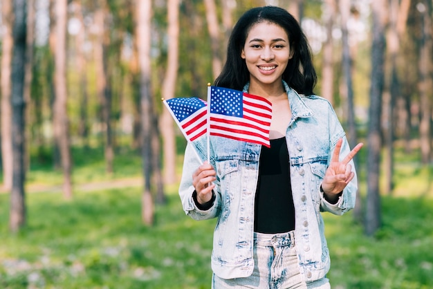 Hispanic woman with usa flags showing peace gesture Free Photo