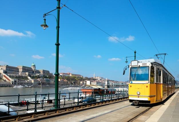 Historical tram runs on the riverside in budapest Premium Photo