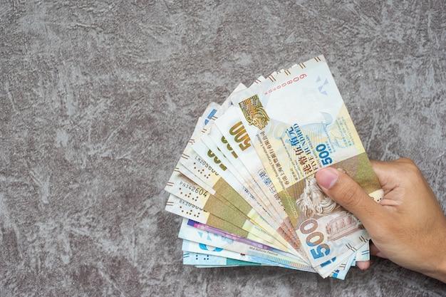 ビジネスの女性の手持ち株香港通貨紙幣、ビジネスの背景のhkドル Premium写真