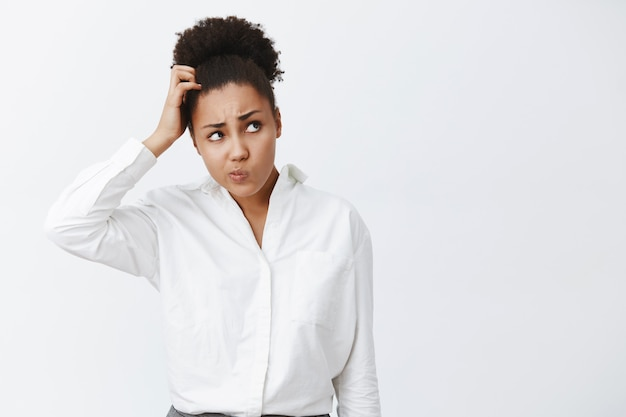 Hmm, i do not know what to do. portrait of questioned unaware or uncertaing cute woman with dark skin and curly hair, scratching head, folding lips and gazing up while thinking, being unsure Free Photo