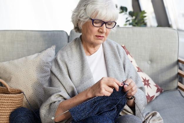 Хобби, досуг и пенсионное понятие. красивая элегантная бабушка в очках сидит на сером диване с иголками, вяжет свитер для внука, с серьезным сосредоточенным взглядом Бесплатные Фотографии
