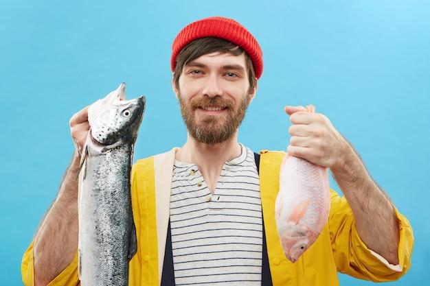 Хобби, отдых, досуг и концепция деятельности. веселый небритый молодой рыбак или рыболов в стильной красочной одежде держит двух только что пойманных рыб, широко улыбается и гордится своим уловом Бесплатные Фотографии