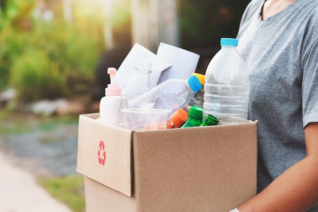 リサイクルのための女性の手holdgingボックスごみ Premium写真