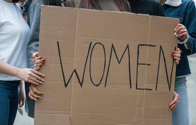 Держа большой плакат. группа женщин-феминисток протестует на открытом воздухе за свои права Бесплатные Фотографии