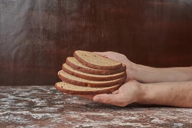 手にパンのスライスを持っています。 無料写真