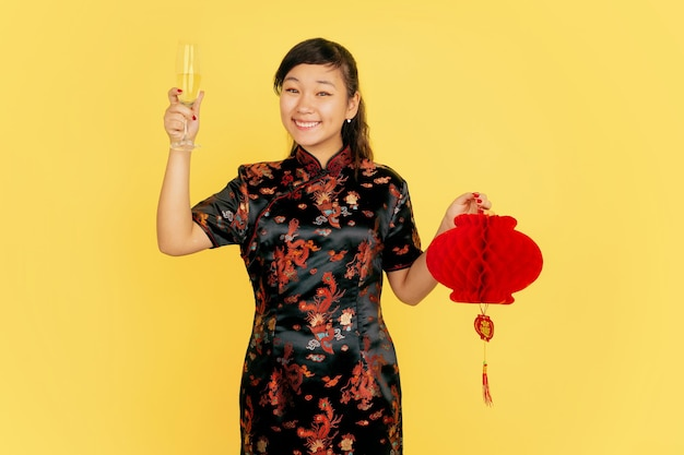 샴페인과 랜턴을 들고. 해피 중국 설날. 노란색 바탕에 아시아 젊은 여자의 초상화. 전통 옷을 입은 여성 모델이 행복해 보입니다. Copyspace. 무료 사진