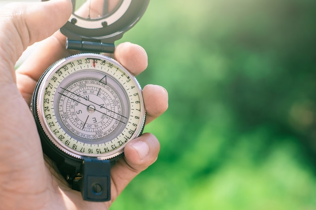 Holding compass on blurred background. using wallpaper or background travel or navigator image. Premium Photo