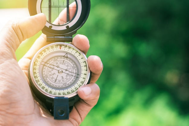 Holding compass on blurred background. Premium Photo