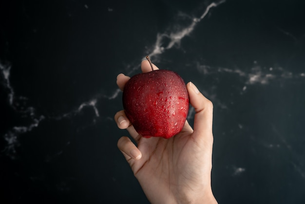 Holding fresh juicy red apple with water spray droplets on apple in hand over a black marble surface. top view flat lay composition. Premium Photo